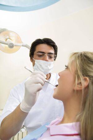 角度のついた: 角度のミラーを保持している歯科医 写真素材