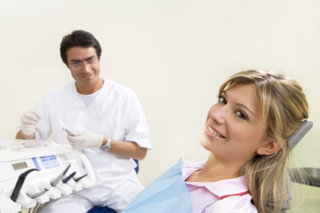 young woman doing dental checkup. Dentist in the background