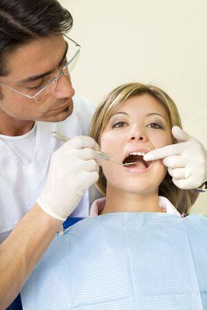 角度のついた: 歯科健診を行う若い女性。歯科医は斜めミラーを使用してください。 写真素材