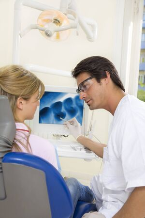 dentist talking to his patient and showing her a x-ray image of her teeth photo