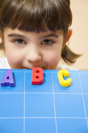abc's: child learning the ABCs. The focus is on the mouth leaning on the blue board Stock Photo
