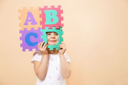 child learning the ABCs. The focus is on her eyes