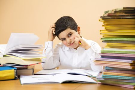 children sad: little boy has troubles with homeworks and is scratching his head