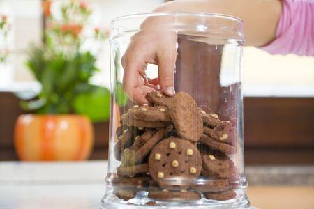 jarra: peque�a muchacha que roba algunas galletas del tarro Foto de archivo