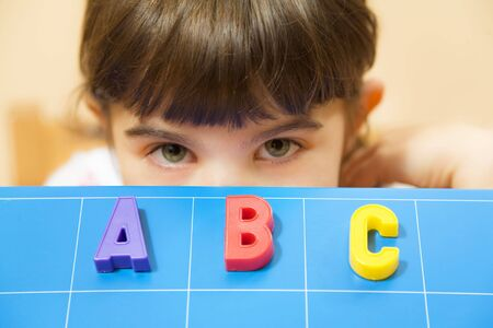 child learning the ABCs. The focus is on the letters Stock Photo