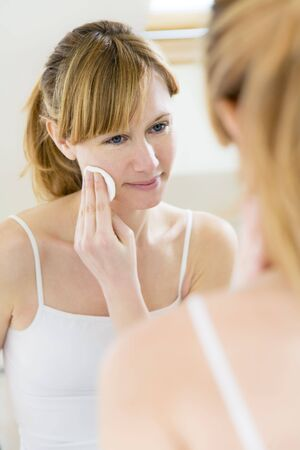 young woman using a cotton pad to remove her make-up Stock Photo