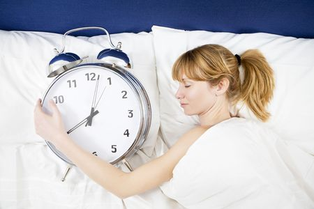 Young woman lying in bed with eyes closed, holding a huge alarm clock Stock Photo - 2913586