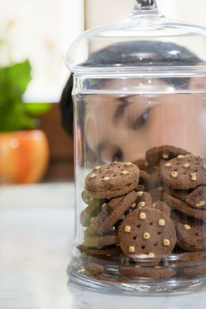 little boy looking at cookies in a jar photo
