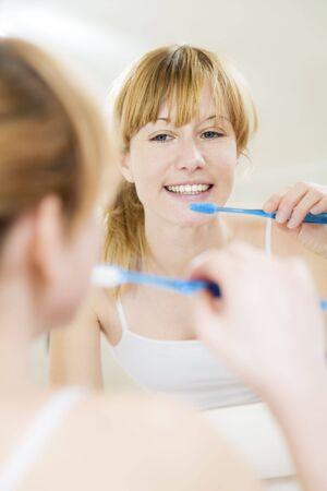 cepillarse los dientes: Joven mujer busca en un espejo, cepill�ndose los dientes