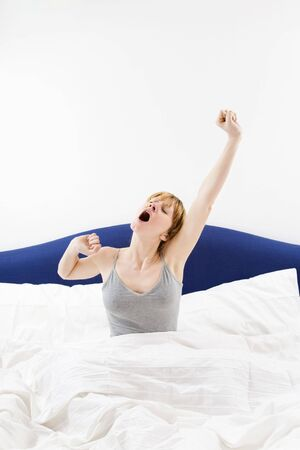 arms above head: Young woman sitting on bed, stretching arms above head and yawning