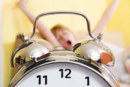 above head: Close up of alarm clock. Young woman in the background stretching arms above head and yawning.