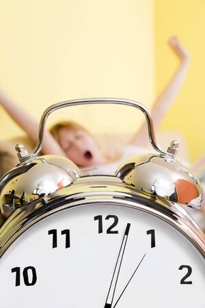 Close up of alarm clock. Young woman in the background stretching arms above head and yawning. Xopy space Stock Photo - 2933627