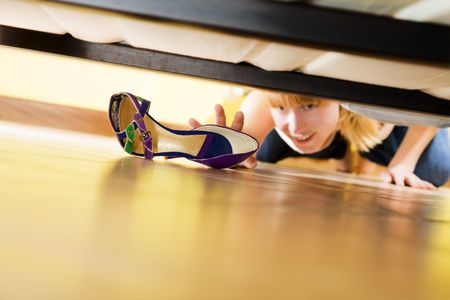 girl bed: woman looking for her shoe under the bed Stock Photo