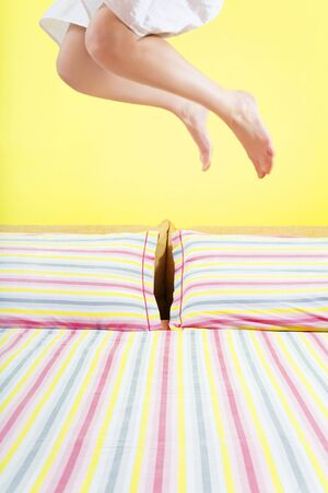 young woman jumping on bed with striped sheet Stock Photo