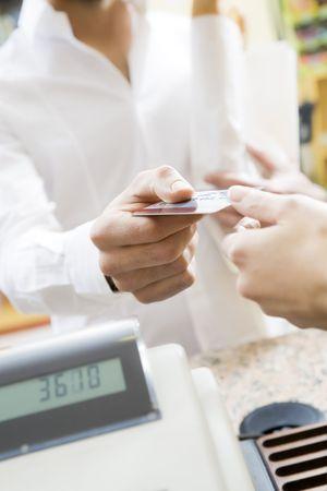 hombre haciendo compras en un supermercado y paga con tarjeta de crédito  Foto de archivo