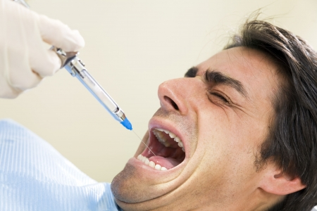 anesthetize: dentist holding a syringe and anesthetizing his terrified patient.