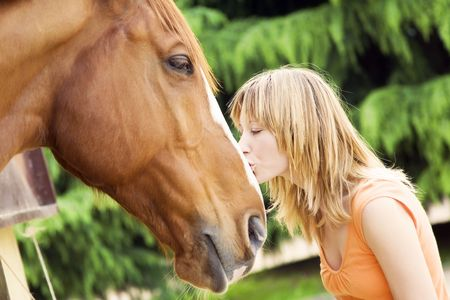 young blond woman kissing a brown horse photo