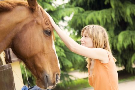 young blond woman stroking a brown horse photo