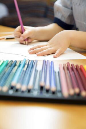 little girl playing with colors. The focus is on the hand lying on the paper Stock Photo - 3004832
