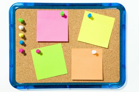 bulletin board and multi colored stickies attached with push pins. Isolated on white and copy space Stock Photo - 3010183
