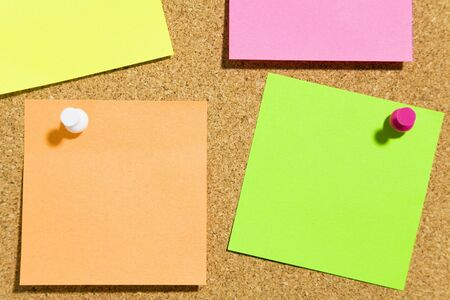bulletin board and multi colored stickies attached with push pins. Copy space Stock Photo - 3010182