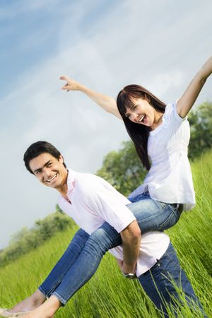 piggyback: Man giving woman piggyback in meadow, laughing. Narrow focus on his eye.