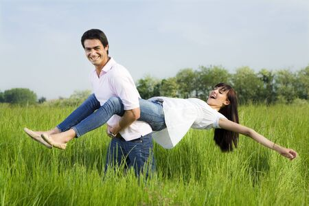 carrying girlfriend: Man giving woman piggyback in meadow, laughing