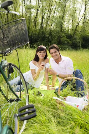 couple having a picnic in a park, smiling and looking at the camera Stock Photo - 3020920