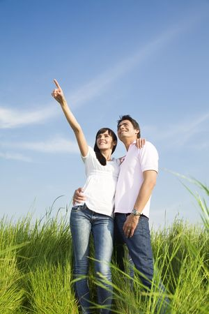 boyfriend: young couple in meadow with hand in air, hugging and smiling. Copy space