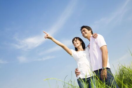 young couple in meadow with hand in air, hugging and smiling. Copy space photo