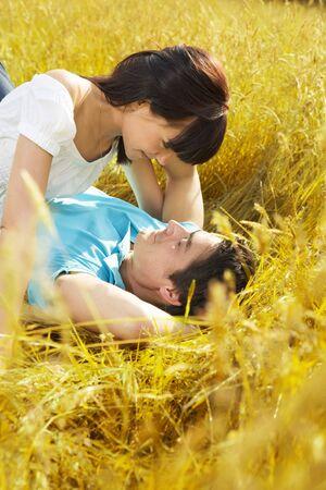people kissing: jeune couple fixant en prairie et serrer  Banque d'images
