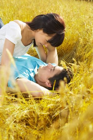couple in summer: young couple laying down in meadow and hugging