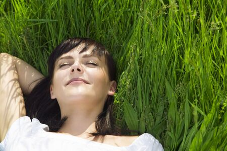 beautiful girl lying down of grass. Copy space photo