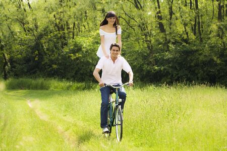 couple biking in park, smiling and hand on shoulders Stock Photo