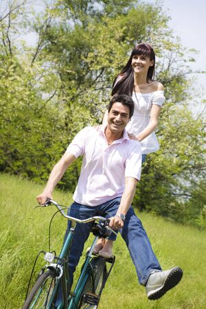 couple biking in park, smiling and hands on shoulder photo