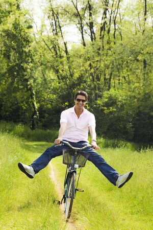 outstretching: man biking in park, smiling and outstretching his legs
