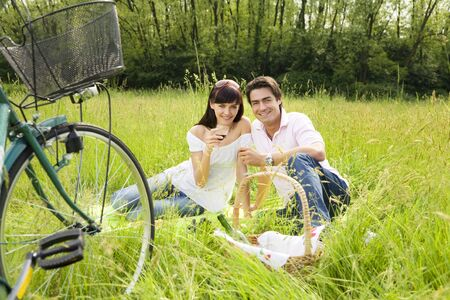 couple having a picnic in a park, smiling and looking at the camera photo