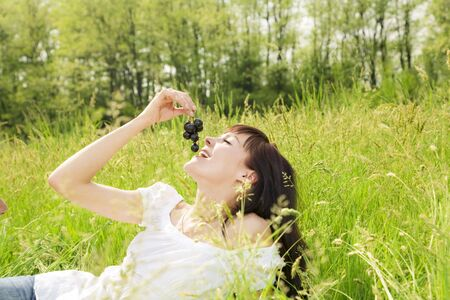 beautiful girl lying down of grass, eating black grapes. Copy space photo