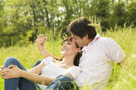 tickling: Couple lying in grass, man tickling her girlfriends nose and smiling