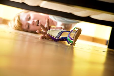 woman looking for her shoe under the bed Stock Photo - 3050561