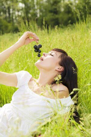 girl lying down: hermosa muchacha acostada de pasto, comiendo uvas negro  Foto de archivo