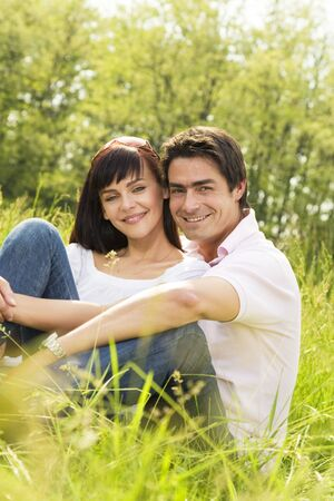 Couple lying in grass, smiling and hugging photo