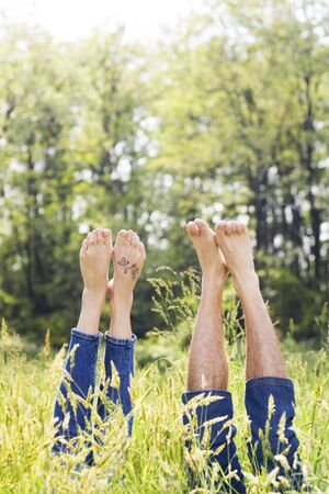 Couple lying in grass stretching their legs up photo