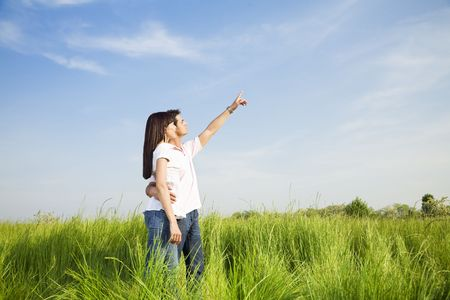 woman pointing: young couple in meadow with hand in air, hugging. Copy space