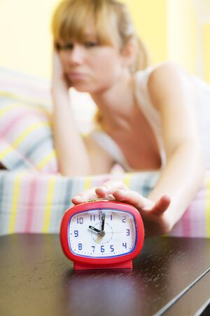 Young woman in bed snoozing a red alarm clock photo