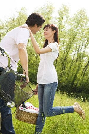 couple in park with holding picnic basket, kissing. Woman raises her leg photo