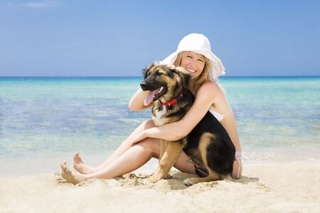 blond woman sitting on sand with black dog