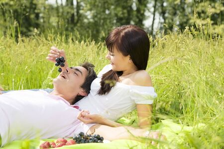 Couple lying in grass, smiling and eating grapes photo