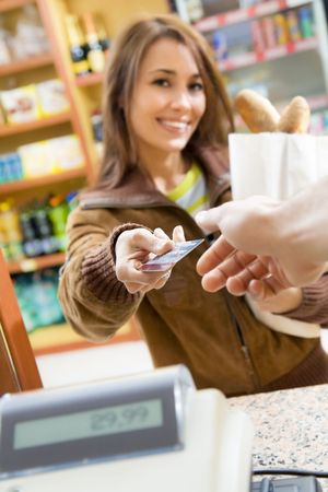 woman doing shopping in a grocery store and paying by credit card Stock Photo