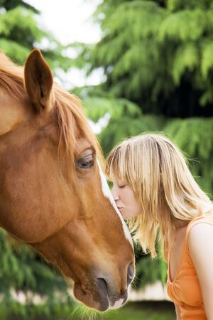 young blond woman kissing a brown horse